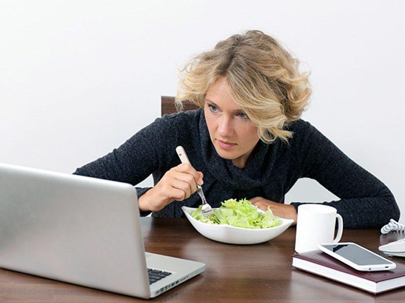 パソコンを見ながら食事をする女性