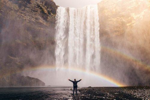 滝の前で手を広げる人