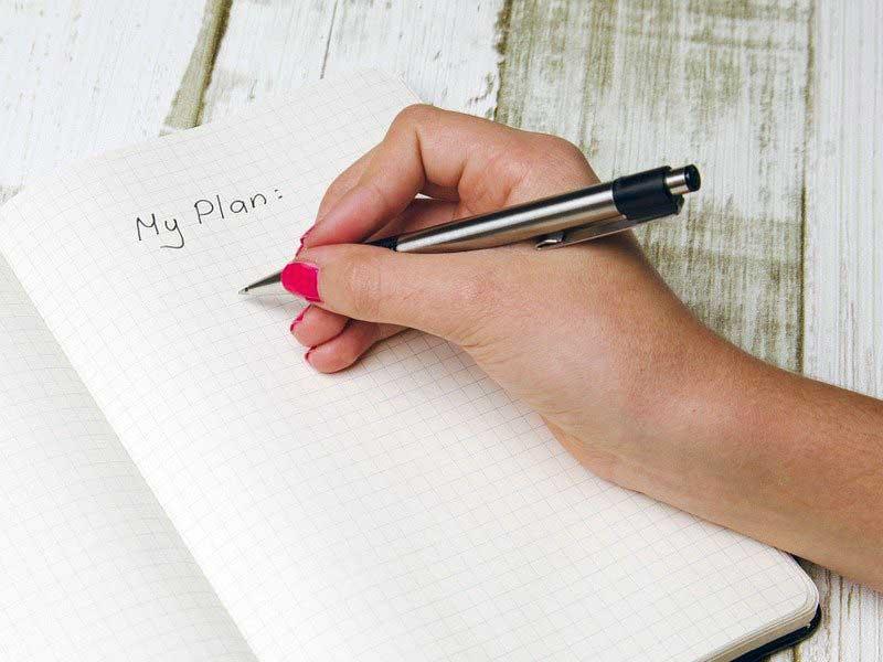 手帳に計画を書き込む人